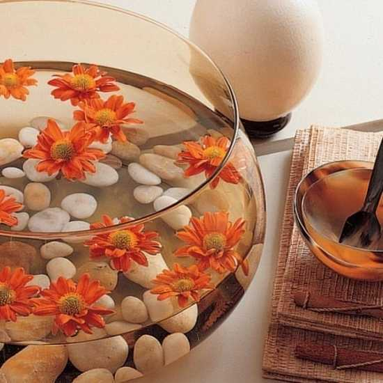 glass bowl with water, floating flowers and white pebbles