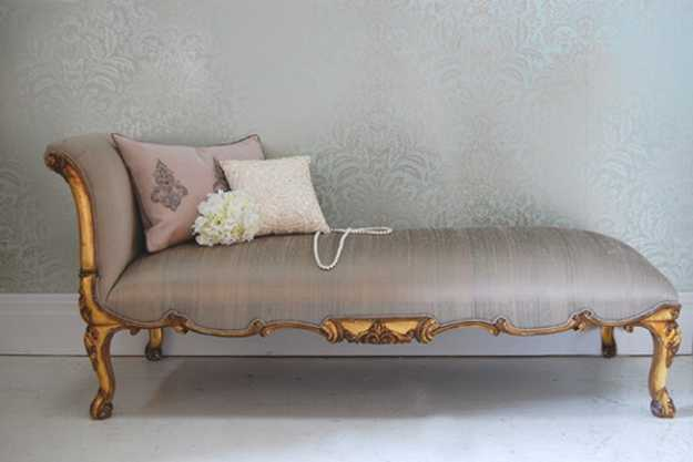 low recamier with golden details, carved wood designs and soft pillows