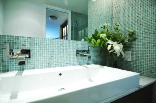 green bathroom mosaic tiles and white flowers