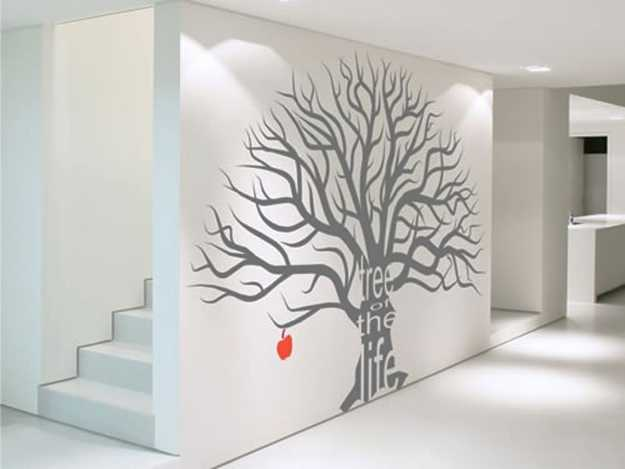 gray tree with red apple on white wall