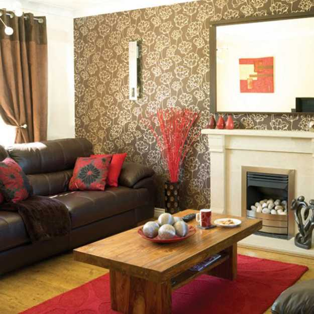 red floor rug and cushions in living room with furnishings and wallpaper in brown color