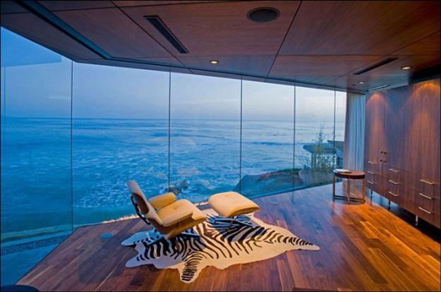 eames lounge chair in room with glass wall