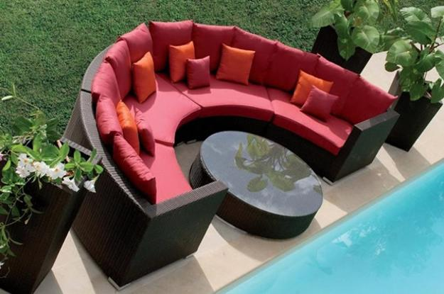 round coffee table and outdoor sofa with red cushions