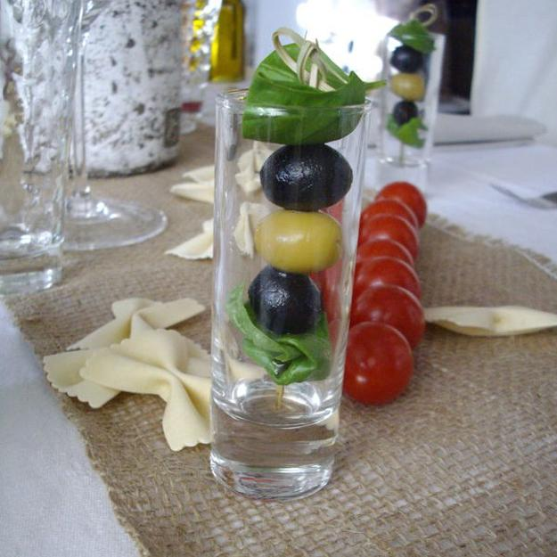 red tomatoes and olives in glasses for table decoration italian style