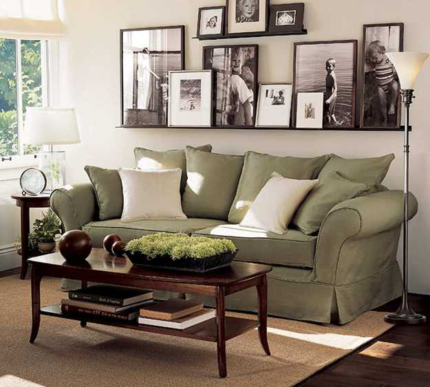 living room sofa in green color and wall decoration with black and white photographs