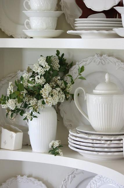 white flowers and white dinnerware set on shelves