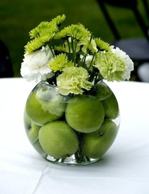 Gorgeous Table Centerpiece Created With Green Apples And Flowers In A Glass Vase Filled With Water