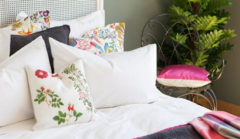 white bedding set with pillows in green and red colors